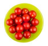 Cereja dos tomates na bacia de vidro verde isolada no fundo branco Fotos de Stock