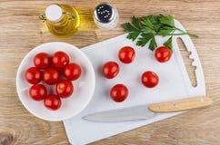 Cereja dos tomates na placa de corte, óleo vegetal, faca, sal Fotos de Stock Royalty Free