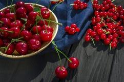 A cereja e os corintos vermelhos encontram-se em um fundo de madeira preto fotografia de stock
