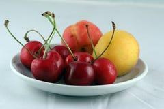 Cereja e pêssegos em uma placa Imagem de Stock