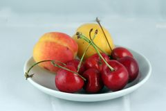 Cereja e pêssegos em uma placa Imagens de Stock Royalty Free