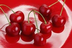 Cereja em um prato vermelho Fotografia de Stock Royalty Free