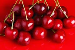 Cereja em um prato vermelho Imagem de Stock