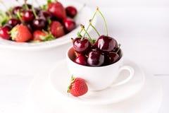 Cereja fresca e bonita em um copo branco Cherry Close Up White Background suculento maduro fotografia de stock