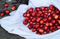 Cereja fresca sobre em uma cobertura branca em um fundo do banco de madeira Cerejas maduras frescas Cerejas doces Fotos de Stock