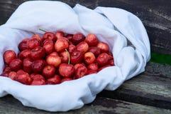 Cereja fresca sobre em uma cobertura branca em um fundo do banco de madeira Cerejas maduras frescas Cerejas doces Fotografia de Stock