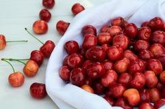 Cereja fresca sobre em uma cobertura branca em um fundo do banco de madeira Cerejas maduras frescas Cerejas doces Imagem de Stock Royalty Free