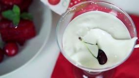 Cereja que cai no movimento lento super da sobremesa do iogurte vídeos de arquivo
