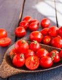 Cereja suculenta vermelha dos tomates na placa de madeira marrom Imagem de Stock