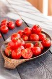 Cereja suculenta vermelha dos tomates na placa de madeira marrom Imagem de Stock Royalty Free