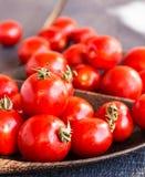 Cereja suculenta vermelha dos tomates na placa de madeira marrom Foto de Stock