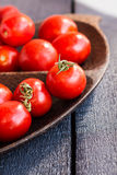 Cereja suculenta vermelha dos tomates na placa de madeira marrom Fotos de Stock