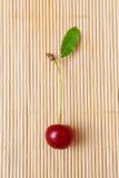 Cereja vermelha no fundo da palha Foto de Stock Royalty Free