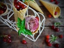 Cerejas caseiros do gelado e chocolate em um cone do waffle, cerejas frescas na tabela de madeira velha Fotos de Stock