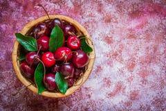 Cerejas com folhas em uma cesta no fundo sarapintado Imagem de Stock