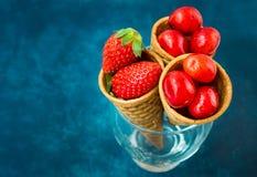 Cerejas doces lustrosas das morangos orgânicas maduras em cones de gelado do waffle no vidro, obscuridade - fundo azul, f saudáve Imagens de Stock Royalty Free