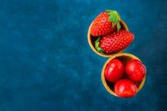 Cerejas doces lustrosas das morangos orgânicas maduras em cones de gelado do waffle, obscuridade - fundo azul, molde Fotografia de Stock
