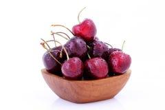 Cerejas doces na bacia de madeira isolada no fundo branco Fotografia de Stock Royalty Free
