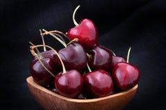 Cerejas doces na bacia de madeira no fundo preto Imagens de Stock Royalty Free