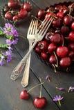 Cerejas e flores na tabela de madeira velha Foto de Stock