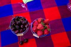 Cerejas e morango em uma cubeta Piquenique na peça da solteira Foto de Stock Royalty Free