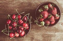 Cerejas e morango orgânicas maduras frescas no fundo de madeira Estilo do vintage e matização rústicos da cor Foto de Stock