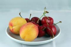 Cerejas e pêssegos em uma placa Imagens de Stock