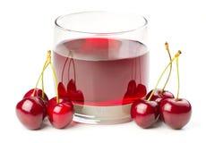 Cerejas e um vidro do suco da cereja foto de stock