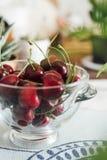 Cerejas ecológicas na bacia de vidro, na tabela Imagens de Stock Royalty Free