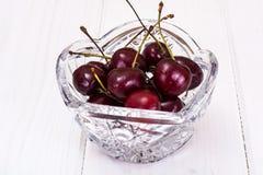 Cerejas em Crystal Bowl no fundo rústico Imagem de Stock