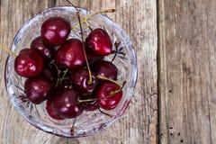 Cerejas em Crystal Bowl no fundo rústico Foto de Stock