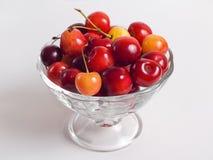 Cerejas em um vaso no fundo branco Fotografia de Stock Royalty Free