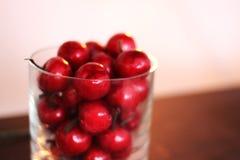 Cerejas em um vidro Escuro - vermelho blurry imagem de stock