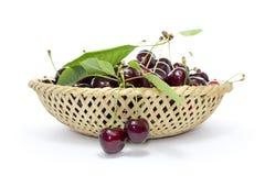 Cerejas em uma cesta de vime com uma folha Imagens de Stock