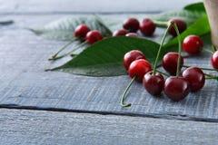 Cerejas frescas doces com as folhas verdes na madeira rústica azul Foto de Stock Royalty Free