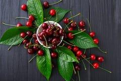 Cerejas frescas doces com as folhas verdes na madeira rústica azul Imagem de Stock