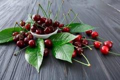 Cerejas frescas doces com as folhas verdes na madeira rústica escura Fotos de Stock