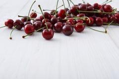 Cerejas frescas doces no fundo de madeira branco Imagens de Stock