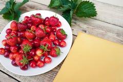 Cerejas frescas e morangos maduras vermelhas em uma placa branca Imagem de Stock