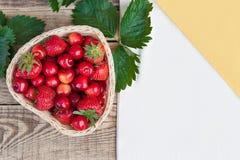 Cerejas frescas e morangos maduras vermelhas em uma placa branca Foto de Stock