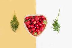 Cerejas frescas e morangos maduras vermelhas em uma placa branca Imagens de Stock Royalty Free