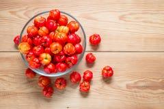 Cerejas frescas em uma bacia de vidro na tabela de madeira Fotografia de Stock