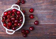 Cerejas frescas em uma bacia na tabela de madeira Foto de Stock