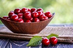 Cerejas frescas na bacia na tabela fotos de stock