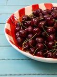 Cerejas frescas na placa vermelha do guingão Imagem de Stock