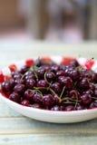 Cerejas frescas na placa vermelha do guingão Fotografia de Stock Royalty Free