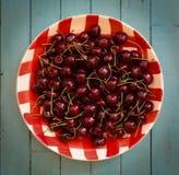 Cerejas frescas na placa vermelha do guingão Imagens de Stock