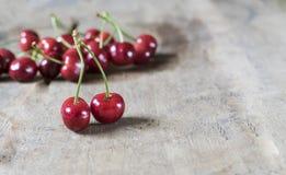 Cerejas frescas no fundo de madeira velho, rústico Fotos de Stock Royalty Free