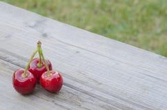 3 cerejas isoladas na madeira Imagem de Stock Royalty Free