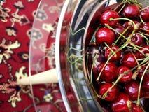 Cerejas maduras doces em uma placa de metal em uma tabela de vidro imagens de stock royalty free